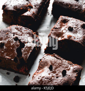 Dark chocolate brownies on baking paper. Closeup view square crop - Stock Photo
