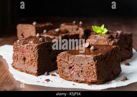 Dark chocolate brownies decorated with mint leaf on wooden table. Closeup view horizontal composition - Stock Photo