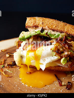 Poached egg sandwich with caramelized onion, avocado, meat and cheese on a wooden cutting board - Stock Photo