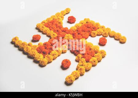 stock photo of hindu auspicious symbol called Swastika made using marigold flower or zendu or genda phool, Flower - Stock Photo