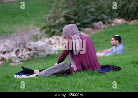 A lone Israeli Arab wearing a hijab with a religious Jewish man in background in Gan Saker or Sacher park in West - Stock Photo