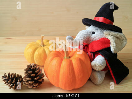Elephant doll in wizard costume with a pair of vivid color ripe pumpkins and two pine cones on wooden table - Stock Photo