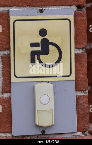 Disabled entry push button - sign on rail way station - Stock Photo