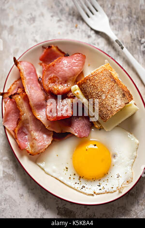 Fried egg, bacon and baguette with mozzarella cheese sandwich. Breakfast plate - Stock Photo