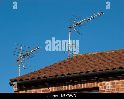 Two TV Aerials on a rooftop set against a clear blue sky - Stock Photo