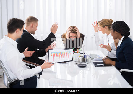 Upset Businesswoman Sitting With Aggressive Colleague In Meeting - Stock Photo