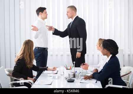 Group Of Businesspeople Looking At Businessman Blaming His Colleague In Meeting - Stock Photo