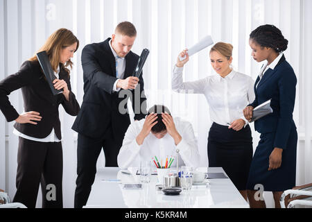 Group Of Angry Businesspeople Blaming Male Colleague In Meeting - Stock Photo