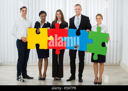 Group Of Businesspeople Holding Multi-colored Puzzle Pieces In Office - Stock Photo