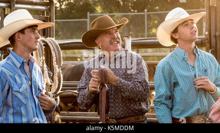 Rodeo Three Authentic Cowboys Looking Up out of frame  dressed in traditional western wear waiting - Stock Photo