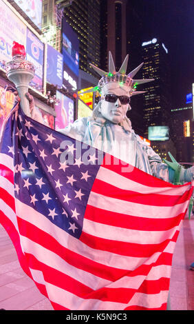New York City, New York - Nov 11, 2014: Mime dressed as Statue of Liberty poses for cameras in Times Square - Stock Photo