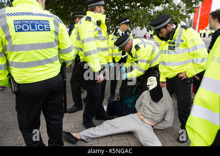 London, UK. 9th September, 2017. Police officers stop and search a man wearing a Guy Fawkes mask during a protest - Stock Photo
