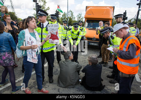 London, UK. 9th September, 2017. Police officers ask protesters who sat down in one of the access roads used by - Stock Photo