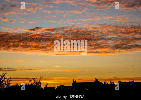 London UK.  10th September 2017.  Residential rooftop buildings are silhouetted against a beautiful  autumn sunrise - Stock Photo