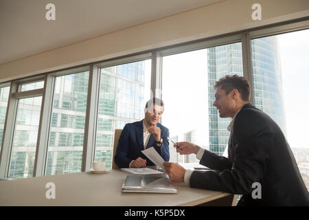 Two businessmen discussing growth rates on meeting - Stock Photo
