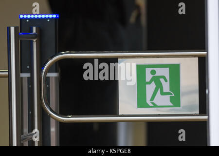 Sign - exit, green emergency exit on turnstile - Stock Photo