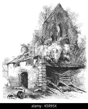 1870: Farmyard with a smallstore shed with wagons attached to ruined Valle Crucis Abbey, a Cistercian abbey located - Stock Photo