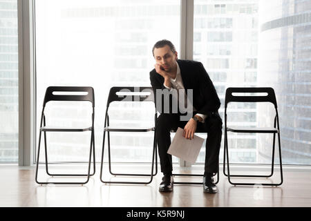 Bored young man in suit sitting in waiting room. - Stock Photo