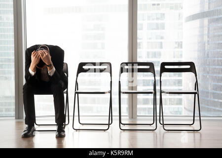 Stressed upset businessman sitting on chair, received bad news. - Stock Photo