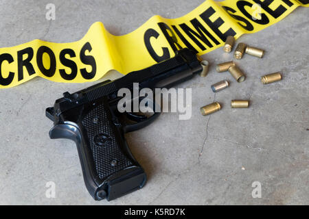 Crime scene concept with black gun and crime scene tape from above - Stock Photo