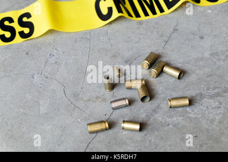 Crime scene concept with crime tape and casings - Stock Photo