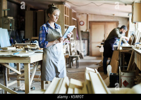 Full length portrait of concentrated young craftswoman in apron standing at spacious workshop and using digital - Stock Photo