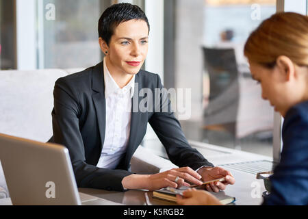 Confident middle-aged entrepreneur conducting negotiations with business partner while sitting at cozy cafe, panoramic - Stock Photo