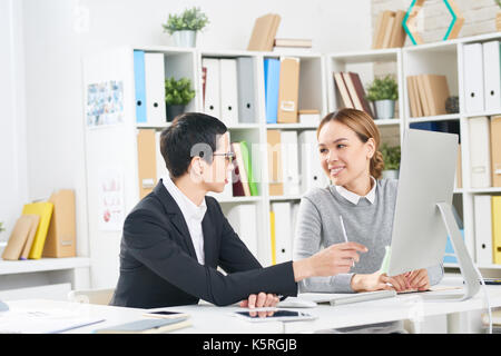 Working process at open plan office: talented financial managers gathered together in front of computer and preparing - Stock Photo