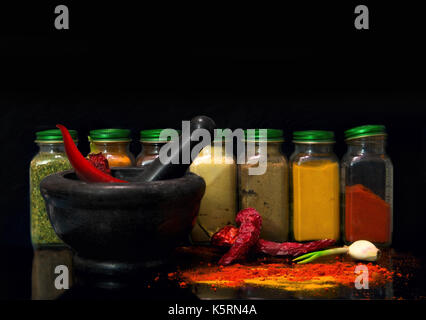 A set of jars with spices and mortar with red pepper on a black background - Stock Photo