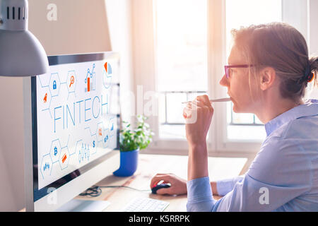 Fintech concept on computer screen with modern interface and innovative charts, female business person at office - Stock Photo