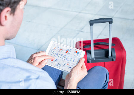 Businessman at airport using digital tablet computer with infographic concept of fintech (financial technology) - Stock Photo