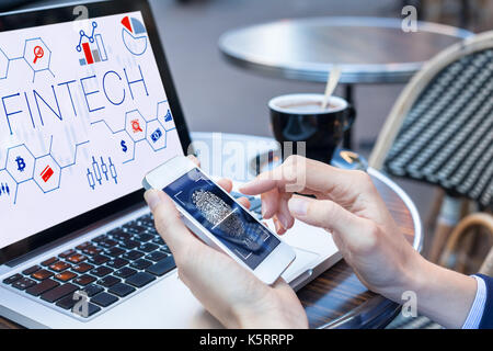 Business person using fingerprint scan on smartphone to access secure data payment on internet with laptop computer - Stock Photo