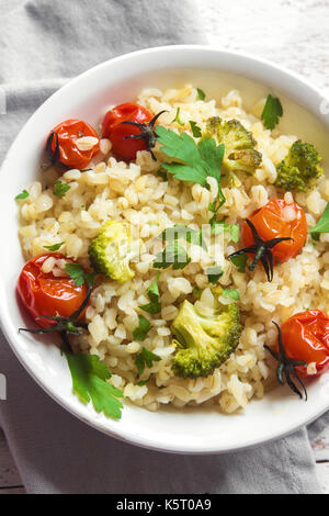 Bulgur with vegetables: tomatoes, carrots, zucchini, broccoli and parsley in rustic wooden bowl - healthy vegetarian - Stock Photo