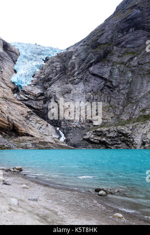 blue water lake coming from a blue ice glacier in norway - Stock Photo
