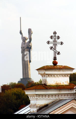 Cross of Kiev-Pechersk Lavra and the monument 'Mother Motherland'  in Kyiv, Ukraine in autumn - Stock Photo