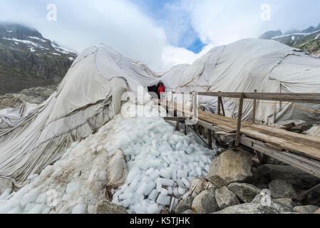 Entrance to the ice tunnel in the Rhone glacier, covered with white cloths against melting, Obergoms, Valais, Switzerland - Stock Photo