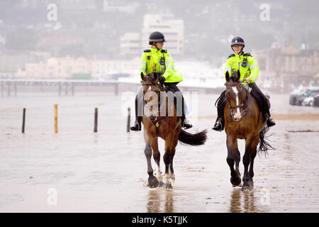 Two Mouned Police Woman, on patrol,  in fluorescent uniforms riding.their Police Horses along a beach in wet windy - Stock Photo