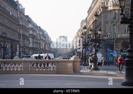 A street view of the Avenue de l'Opéra with Banque Solfea on the right and Hôtel du Louvre (Hyatt) in the background. - Stock Photo