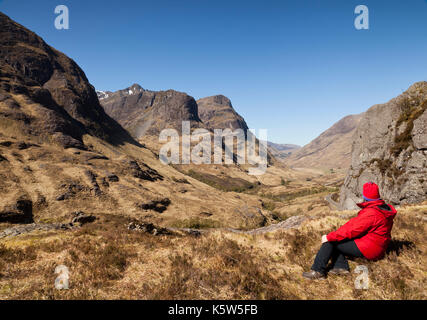 A woman sitting admiring the view at The Study, Three sisters of Glencoe, Scotland, UK - Stock Photo