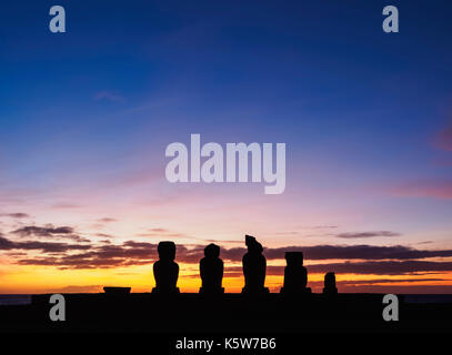 Moais in Ahu Vai Uri at sunset, Tahai Archaeological Complex, Rapa Nui National Park, Easter Island, Chile - Stock Photo