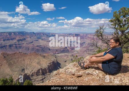 Asian woman enjoying the view on the south rim of the Grand Canyon, Arizona - Stock Photo