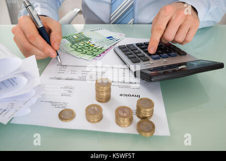 Close-up Of Businessman Calculating Invoice With Money At Desk - Stock Photo