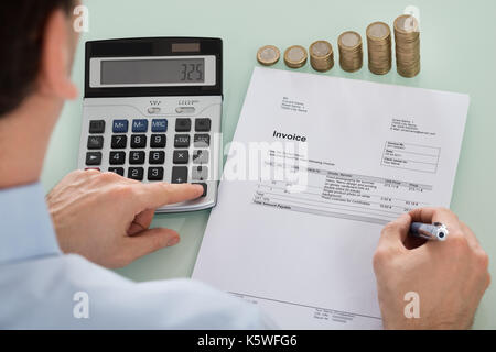 Close-up Of Businessperson Calculating Invoice With Coins At Desk - Stock Photo