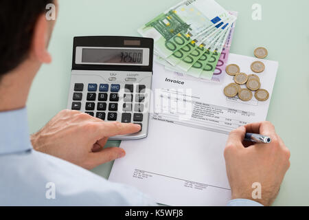 Close-up Of Businessman Examining Invoice With Money At Desk - Stock Photo