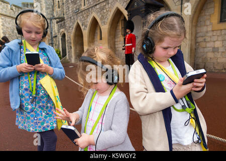 Three sisters /children /kid /kids on holiday listen to an audio guide information while on a tour inside the walls - Stock Photo