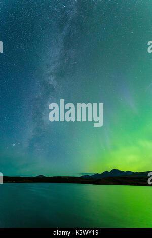 Milky Way and Aurora Borealis above the Alaska Range mountains at Round Tangle Lake along the Denali Highway in - Stock Photo