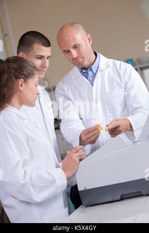man with two young students in white jackets - Stock Photo