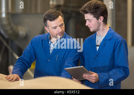 manager and apprentice in factory storeroom - Stock Photo