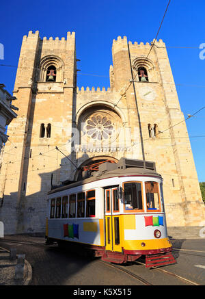 Famous yellow tram running in front of Se Cathedral in Lisbon, Portugal - Stock Photo