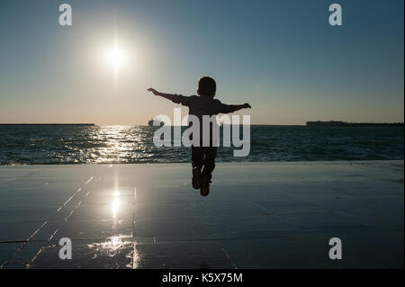 Silhouette of a small jumping boy on a background of sea sunset with a ship on the horizon - Stock Photo